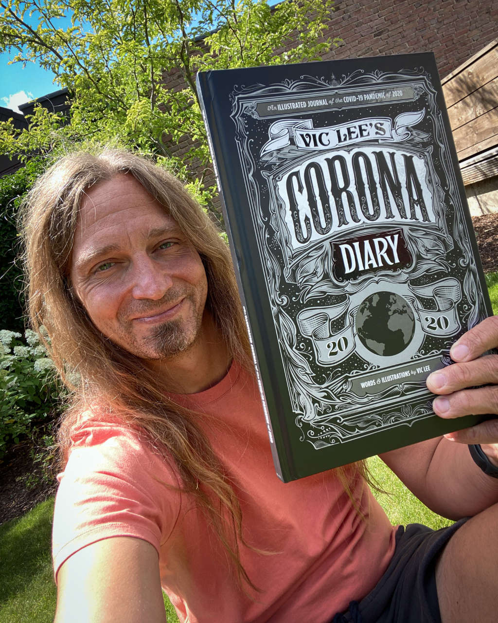 The photo showing me holding up the Corona Diary 2020 by Vic Lee, a book full of illustrations by him.