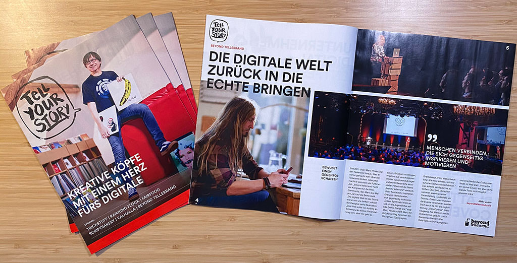 """A photo showing a small pile of magazines on the left with its cover page and the title """"Tell Your Story"""". Next to it lies an open version on the right side with an interview of Marc Thiele about beyond tellerrand."""