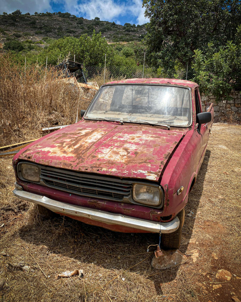 Photo showing an old abandoned car in the backyard of our house on Crete