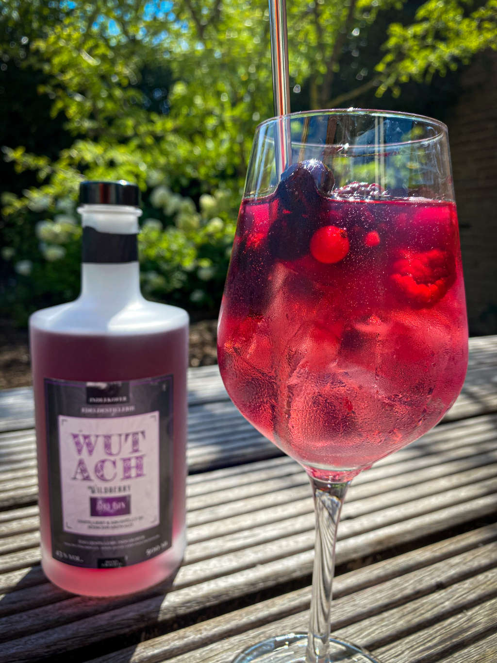 The photo showing a glas with red gin and tonic in a glas with ice cubes and wild berries. In the back a bottle of the gin.