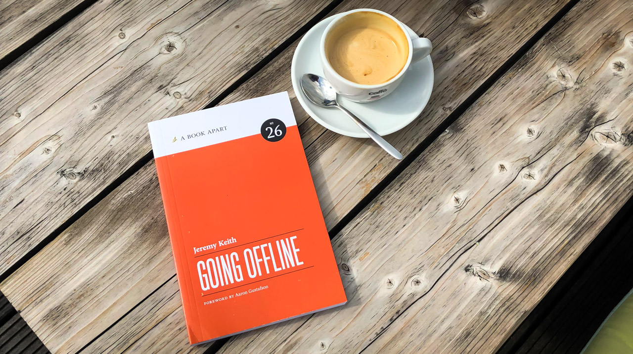 "Photo showing the book ""Going Offline"" and a cup of coffee on a wooden table"