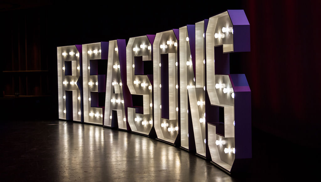 Light sign on stage of Reasons To